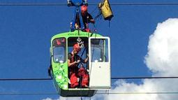 Penumpang dengan membawa anak kecil dikeluarkan dari kereta gantung saat proses evakuasi di Koln, Jerman, Minggu (30/7). 32 kereta gantung mendadak terhenti usai menabrak tiang penyangga hingga membuat penumpangnya terjebak. (Martin Oversohl/dpa via AP)
