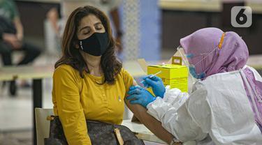 Petugas menyuntikkan vaksin COVID-19 kepada pedagang di Pasar Tanah Abang Blok A, Jakarta, Kamis (25/2/2021). Menkeu Sri Mulyani optimis pertumbuhan ekonomi Indonesia tahun ini ada pada 4,5-5,3 persen karena adanya dukungan program vaksinasi COVID-19 sebagai penentu. (Liputan6.com/Faizal Fanani)
