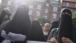 Demonstran melakukan protes larangan penggunaan cadar di Kopenhagen, Rabu (1/8). Parlemen Denmark mengesahkan undang-undang yang melarang pengenaan penutup muka bagi perempuan di tempat umum pada Mei 2018. (Mads Claus Rasmussen/Ritzau Scanpix via AP)