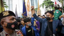 Mahasiswa yang tergabung dalam Aliansi BEM Seluruh Indonesia (BEM SI) dijaga polisi saat menggelar aksi di sekitar Gedung Merah Putih KPK, Jakarta, Senin (27/9/2021). Polisi menahan mahasiswa untuk merangsek maju. (Liputan6.com/Faizal Fanani)