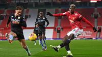 Gelandang Manchester United, Paul Pogba (kanan) melepaskan umpan di depan bek Aston Villa, Matty Cash dalam laga lanjutan Liga Inggris 2020/21 pekan ke-17 di Old Trafford, Jumat (1/1/2021). Manchester United menang 2-1 atas Aston Villa. (AFP/Laurence Griffiths/Pool)