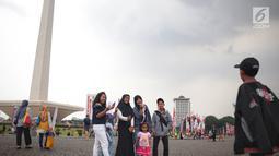 Sejumlah pengunjung berswafoto saat mengunjungi Monumen Nasional (Monas), Jakarta, Sabtu (22/12). Libur sekolah yang berbarengan dengan libur Natal dan Tahun Baru dimanfaatkan masyarakat untuk pergi berwisata ke Monas. (Liputan6.com/Faizal Fanani)