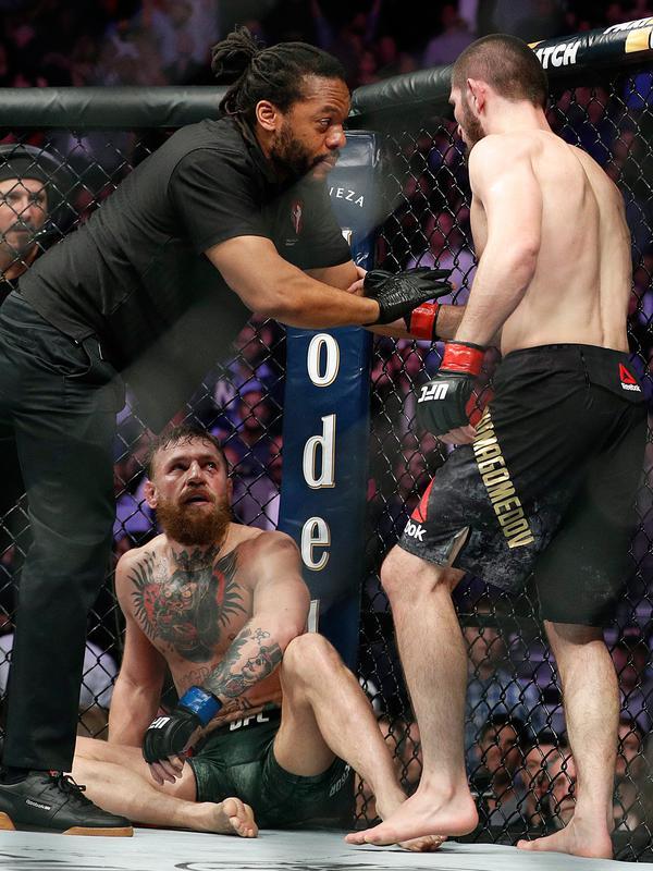 Khabib Nurmagomedov (kanan) ditahan oleh wasit Herb Dean setelah bertarung melawan Conor McGregor selama pertarungan UFC 229 di Las Vegas, AS (6/10). Nurmagomedov menang atas McGregor di ronde keempat. (AP Photo/John Locher)#source%3Dgooglier%2Ecom#https%3A%2F%2Fgooglier%2Ecom%2Fpage%2F%2F10000
