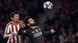 Gelandang Liverpool, Mohamed Salah, berebut bola dengan bek Atletico Madrid, Stefan Savic, pada leg pertama 16 besar Liga Champions di Stadion Wanda Metropolitano, Madrid, Rabu (19/2) dini hari WIB. Atletico menang 1-0 atas Liverpool. (AFP/Pierre Philippe Marcou)