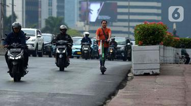 Seorang pria mengendarai skuter listrik di jalanan Jakarta, Jumat (22/11/2019). Pemprov DKI Jakarta saat ini sedang mengkaji aturan mengenai penggunaan skuter listrik di Ibu Kota. (merdeka.com/Imam Buhori)