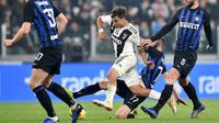Striker Juventus, Paulo Dybala, berusaha melewati pemain Inter Milan pada laga Serie A di Stadion Allianz, Turin, Jumat (7/12). Juventus menang 1-0 atas Inter Milan. (AP/Andrea Di Marco)
