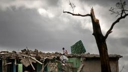 Seorang pria mencari barang miliknya di sebuah bangunan yang hancur dihantam badai tornado di Regla, Kuba (28/1). Hantaman tornado mengakibatkan rumah-rumah hancur berantakan, mobil bergelimpangan hingga pepohonan tumbang. (AP Photo/Ramon Espinosa)