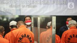 Tersangka dihadirkan saat rilis pengungkap penyebaran uang palsu di Gedung Lobby Bareskrime Mabes Polri, Jakarta, Kamis (23/9/2021). Pemalsuan dan peredaran uang palsu dilakukan sejak Agustus-September 2021 sebanyak 20 orang diamankan dan ditetapkan sebagai tersangka. (Liputan6.com/Faizal Fanani)