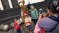 Pengunjung berpose dengan manusia patung di kawasan Museum Fatahilah, Kota Tua, Jakarta, Jumat (16/2). Libur Imlek 2018 dimanfaatkan warga untuk berwisata di sejumlah lokasi, Salah satu yang ramai dikunjungi yakni Kota Tua (Liputan6.com/Immanuel Antonius)