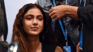 Seorang model saat ditata rambutnya oleh kru makeup di belakang panggung sebelum tampil di catwalk selama Lakmé Fashion Week (LFW) Summer Resort 2019 di Mumbai, India (31/1). (AFP Photo/Sujit Jaiswal)