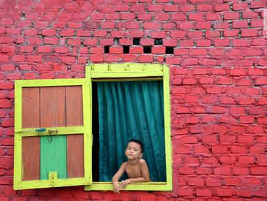 Seorang bocah melongok keluar jendela di Kampung Warna Warni Lubuklinggau, Sumatera Selatan, Rabu (10/1). Kampung yang dulunya menjadi pusat perjudian, sabung ayam, dan lokasi transaksi narkoba itu kini telah berubah wajah (Liputan6.com/Immanuel Antonius)