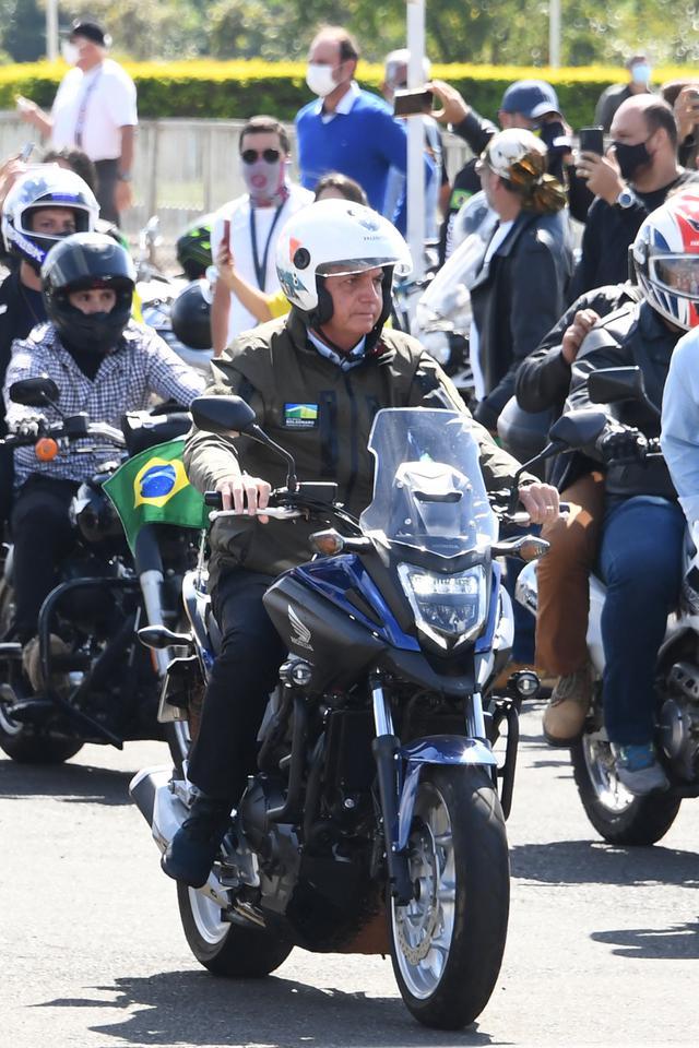 Presiden Brasil Jair Bolsonaro memimpin konvoi ratusan pengendara motor saat melakukan tur di Brasilia, di tengah COVID-19, Minggu (9/5/2021). Bolsonaro melakukan perjalanan dari istana presiden di Brasilia selama satu jam mengelilingi ibu kota Brasil untuk memperingati Hari Ibu. (EVARISTO SA/AFP)
