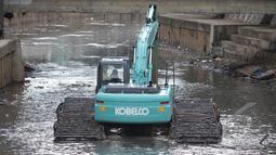Sebuah ekskavator dikerahkan Pemprov DKI untuk mengeruk lumpur di kali inspeksi Ciliwung, Jakarta, Selasa (3/3/2015). Pengerukan dilakukan untuk menjaga sungai tetap baik dan lancar. (Liputan6.com/Faizal Fanani)