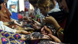 Sejumlah wanita Pakistan membuat henna dengan pacar di salon kecantikan menjelang Hari Raya Idul Fitri di Karachi (3/6/2019). Umat Muslim di seluruh dunia sedang bersiap untuk merayakan Hari Raya Idul Fitri, yang menandai akhir bulan puasa Ramadan. (AFP Photo/Asif Hassan)