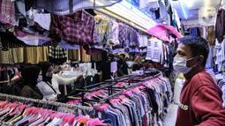 Pedagang mengamati pengunjung memilih pakaian bekas impor di Pasar Senen, Jakarta, Kamis (4/3/2021). Sepinya penjualan diperparah dengan rumor pakaian bekas impor berpotensi menyebarkan virus COVID-19. (merdeka.com/Iqbal S. Nugroho)