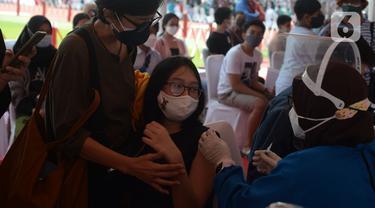 Seorang ibu mendampingi anaknya melakukan vaksin covid-19 di Stadion Utama Gelora Bung Karno (GBK), Senayan, Jakarta, Sabtu (3/7/2021). Pemprov DKI menggelar vaksinasi COVID-19 massal bagi anak usia 12-17 tahun di Stadion GBK selama dua hari, yakni pada 3-4 Juli 2021. (merdeka.com/Imam Buhori)