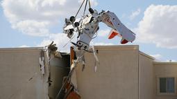 Pesawat bermesin tunggal dievakuasi setelah menabrak gedung di Bandara Regional Ak-Chin, Maricopa, Arizona, Amerika Serikat, Selasa (10/9/2019). Seorang instruktur dan seorang siswa penerbang dibawa ke rumah sakit akibat kecelakaan tersebut. (AP Photo/Ross D. Franklin)