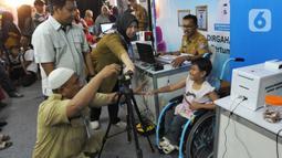 Petugas Disdukcapil Kota Tangerang Selatan melakukan pemotretan kartu identitas anak (KIA) untuk anak penderita Spina Bifida di  Lapangan Skadron 21 Sena Penerbad, Tangerang Selatan, Banten (25/11/2019). Sekitar 500 anak melakukan pembuatan KIA secara gratis. (merdeka.com/Arie Basuki)