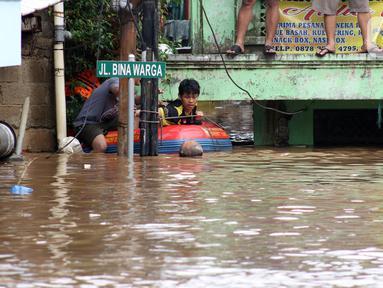 Warga menggunakan perahu karet berusaha keluar dari salah satu gang di Kawasan Rawajati yang tergenang banjir, Jakarta, Rabu Rabu (1/1/2020). Hujan yang mengguyur Jakarta sejak Selasa sore (31/12/2019) mengakibatkan banjir di sejumlah titik di Jakarta. (Liputan6.com/Helmi Fithriansyah)