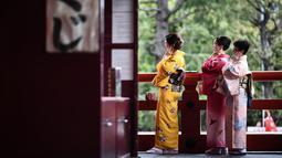 Gambar pada 21 Oktober 2019 menunjukkan sejumlah perempuan mengenakan pakaian tradisional Jepang, kimono, saat mengunjungi kuil Senso-ji di Tokyo. Sensoji Temple merupakan salah satu kuil tertua di Jepang yang terletak di Asakusa. (Anne-Christine POUJOULAT / AFP)