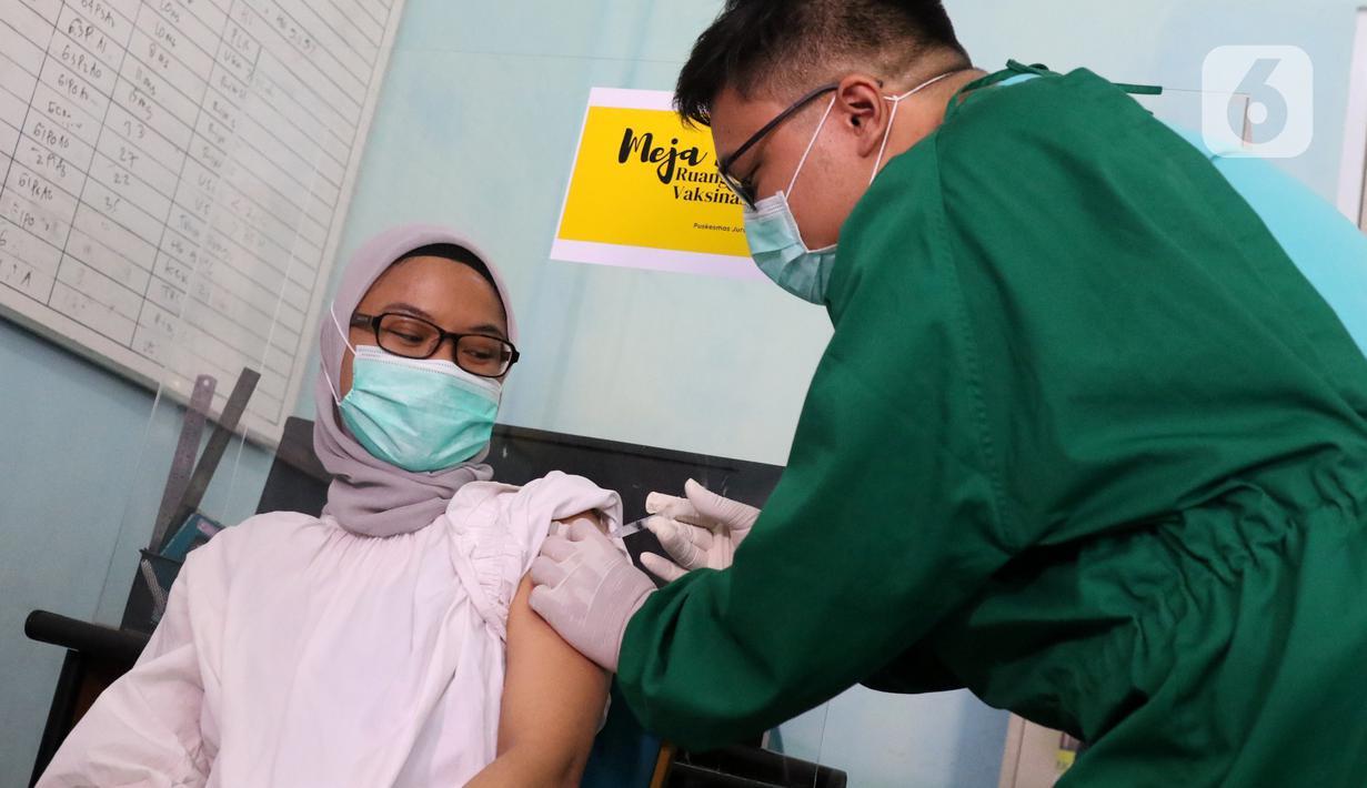 Vaksinator menyuntikkan vaksin COVID-19 kepada tenaga kesehatan yang bertugas di Puskesmas Jurang Mangu, Tangerang Selatan, Jumat (15/1/2021). Program vaksinasi COVID-19 tahap pertama kepada tenaga kesehatan mulai dilakukan di berbagai daerah di Indonesia. (Liputan6.com/Angga Yuniar)