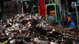 Petugas mengeruk sampah menggunakan alat berat di pintu air Manggarai, Jakarta, Selasa (4/12). Tingginya intensitas hujan di wilayah Jabodetabek membuat sampah yang terbawa arus sungai menumpuk di Pintu Air Manggarai. (Liputan6.com/Faizal Fanani)