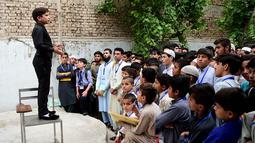 Motivator cilik Hammad Safi berdiri di atas kursi memberikan motivasi kepada para siswa di sebuah akademi bahasa di Peshawar, Pakistan (3/4). Berkat Hammad Safi aksinya di depan umum ia menjadi bintang internet. (AFP/Abdul Majeed)