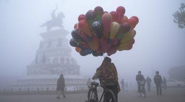 Seorang penjual balon berjalan di sepanjang jalan Heritage di tengah kabut tebal di hari yang dingin di Hari Tahun Baru, di Amritsar (1/1/2021). Gelombang Dingin, Kabut Tebal Mencengkeram India Utara di Hari Tahun Baru di Delhi. (AFP/Narinder Nanu)