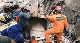 Petugas Basarnas mencari korban di reruntuhan bangunan yang rusak di Mamuju, Sulawesi Barat, Sabtu (16/1/2021). Jalan dan jembatan yang rusak, pemadaman listrik, dan kurangnya alat berat menghambat evakuasi setelah gempa bermagnitudo 6,2 SR yang melanda Majene- Mamuju. (AP Photo/ Sadly Ashari Said)