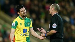 Pemain Norwich City, Graham Dorrans menerima kartu kuning dari wasit Mike Dean saat timnya melawan Manchester City pada Babak ketiga Piala FA di Stadion Carrow Road, Norwich, Sabtu (9/1/2016).  (Reuters/Alex Morton)