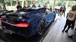 Pengunjung mengamati replika mobil Bugatti Chiron dari jutaan balok Lego Technic pada sebuah pameran di Taman Gorky Moskow, Selasa (23/7/2019). Mobil replika ini bisa dikendarai oleh dua orang dan mampu berakselerasi hingga kecepatan 20 km/jam. (Alexander NEMENOV/AFP)