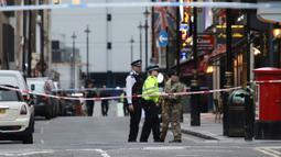 Polisi berjaga menyusul penemuan bom Perang Dunia II di kawasan Soho, London, Inggris, Senin (3/2/2020). Polisi menutup sejumlah jalan dekat lokasi penemuan bom yang merupakan kawasan sibuk di London tersebut. (Philip Toscano/PA via AP)