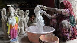 Seorang wanita memberikan warna dasar istri dewa Hindu Rama, dewi Sita di sebuah lokakarya di Hyderabad, India (15/3). Festival Rama Navami tersebut untuk merayakan kelahiran dewa Rama di seluruh India. (AFP/Noah Seelam)