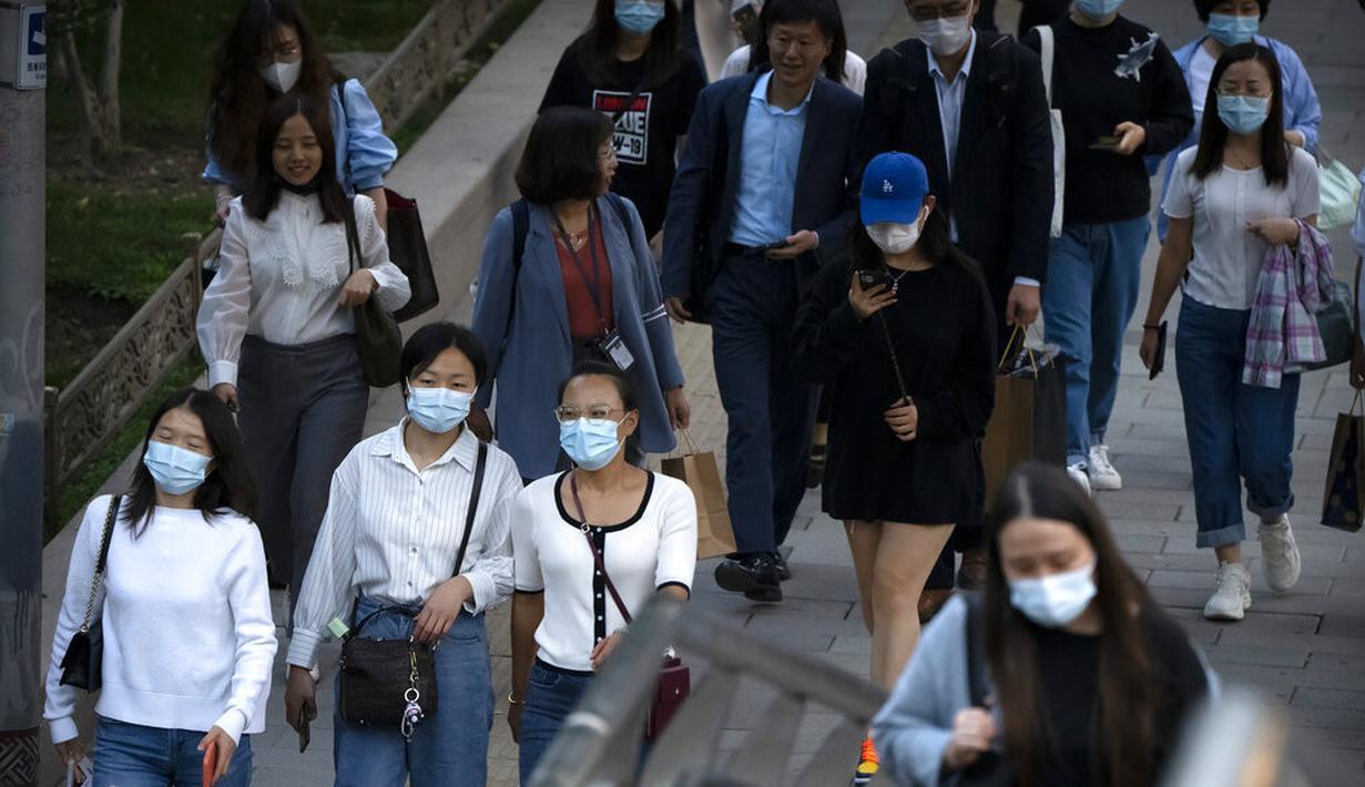 Orang-orang memakai masker berjalan di sepanjang jalan di kawasan pusat bisnis di Beijing (16/9/2021).  China pada Kamis (15/9) melaporkan beberapa lusin tambahan kasus virus corona yang ditularkan secara lokal saat berfungsi untuk menahan wabah di provinsi timur Fujian (AP Photo/Mark Schiefelbein)