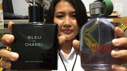 Petugas menunjukkan parfum palsu berbagai merek di kawasan Tamansari, Jakarta Barat, Rabu (7/2). Dalam penggerebekan tersebut polisi mengamankan barang bukti berupa ribuan botol parfum merek terkenal. (Liputan6.com/Immanuel Antonius)
