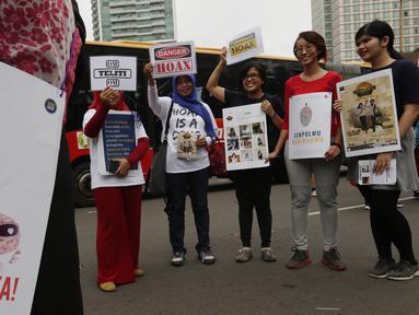 Masyarakat Anti Fitnah Indonesia (Mafindo) menunjukan poster di hari bebas kendaraan bermotor di kawasan Thamrin, Jakarta, Minggu (22/1). Aksi tersebut digelar untuk menghimbau masyarakat terkait berita hoax yang marak beredar. (Liputan6.com/JohanTallo)