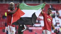 Gelandang Manchester United, Paul Pogba (kiri) dan Amad Diallo membentangkan bendera Palestina usai berakhirnya laga lanjutan Liga Inggris 2020/2021 pekan ke-37 melawan Fulham di Old Trafford Stadium, Rabu (18/5/2021). Manchester United bermain imbang 1-1 dengan Fulham. (AP/Laurence Griffiths/Pool)