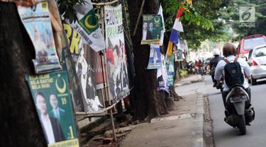 Sejumlah alat peraga kampanye (APK) terpasang di sisi Jalan RS Fatmawati Raya, Jakarta, Selasa (5/3). Pemasangan APK terlihat sembarangan dan tumpang tindih tanpa mempertimbangkan unsur mempertimbangkan estetika. (Liputan6.com/Helmi Fithriansyah)