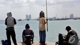 Sejumlah warga asyik memancing di kawasan Pelabuhan Muara Baru, Jakarta, Minggu (11/1/2015). (Liputan6.com/Faizal Fanani)