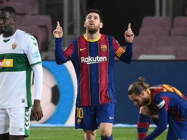 Striker Barcelona, Lionel Messi melakukan selebrasi usai mencetak gol pertama timnya ke gawang Elche dalam laga lanjutan Liga Spanyol 2020/21 pekan ke-24 di Camp Nou Stadium, Barcelona, Rabu (24/2/2021). Barcelona menang 3-0 atas Elche. (AFP/Lluis Gene)