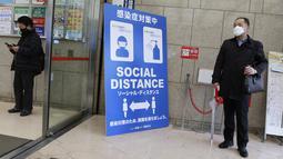 Warga memakai masker untuk melindungi dari penyebaran virus corona menjaga jarak sosial di pintu masuk sebuah gedung di Tokyo (8/3/2021). Pemerintah Jepang memperpanjang keadaan darurat di wilayah Tokyo hingga 21 Maret karena sistem medis masih disaring oleh pasien COVID-19. (AP Photo/Koji Sasahara)