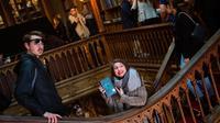 Seorang wanita memegang buku Harry Potter di toko buku Lello, Porto, Portugal, Sabtu (12/1). Toko buku Lello diduga menginspirasi JK Rowling untuk menulis Harry Potter. (MIGUEL RIOPA/AFP)