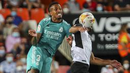 Bek Real Madrid, Eder Militao berebut bola dengan gelandang Valencia, Goncalo Guedes pada lanjutan La Liga di Stadion Mestalla, Senin (20/9/2021) dini hari WIB. Real Madrid menang 2-1 secara dramatis atas Valencia. (AP Photo/Alberto Saiz)