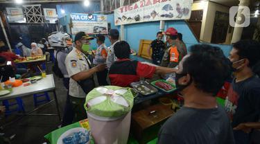 Petugas Gabungan melakukan penertiban penerapan PSBB tempat makan yang masih menyediakan tempat konsumen di wilayah Kecamatan Pulogadung, Jakarta, Jumat (18/9/2020). Malam, Razia dilakukan memastikan ketidakadaannya konsumen makan ditempat tersebut. (merdeka.com/Imam Buhori)