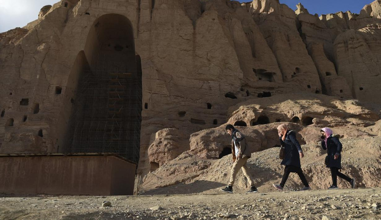 Orang-orang Hazara berjalan di situs patung Buddha raksasa yang dihancurkan oleh Taliban pada 2001 di Provinsi Bamiyan, Afghanistan, 3 Maret 2021. Terletak di jantung pegunungan Hindu Kush, di tebing indah lembah Bamiyan terdapat gua yang berisi kuil, biara, dan lukisan Buddha. (BANGUN KOHSAR/AFP)