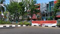 Sejumlah spanduk bertuliskan kata-kata mengingatkan demonstran bertebaran di sejumlah titik di Surabaya, Jawa Timur, Selasa, (20/10/2020). (Foto: Liputan6.com/Dian Kurniawan)
