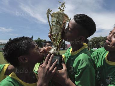 Para pemain SSB Maehanu merayakan gelar juara Liga Remaja UC News setelah mengalahkan SSB Tulehu Putra pada laga final di Lapangan Masariku Yonif 733, Ambon, Kamis (30/11/2017). SSB Maehanu menang 1-0 atas SSB Tulehu putra. (Bola.com/Peksi Cahyo)