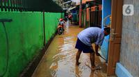 Warga membersihkan lumpur sisa banjir di kawasan Bidara Cina, Kecamatan Jatinegara, Jakarta Timur, Selasa (25/2/2020). Baru satu hari air surut, kawasan Bidara Cina yang bersebelahan dengan Kali Ciliwung kembali mengalami banjir. (merdeka.com/magang/ Muhammad Fayyadh)