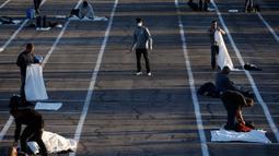 Tunawisma bersiap tidur di tempat-tempat yang ditandai dengan kotak-kotak untuk social distancing di lahan parkir di Las Vegas, Senin (30/3/2020). Lahan parkir itu menggantikan salah satu tempat penampungan lokal yang ditutup setelah seorang penghuni dinyatakan positif virus corona. (AP/John Locher)