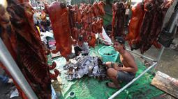Pedagang menyiapkan babi panggang untuk perayaan Tahun Baru Imlek di Phnom Penh, Kamboja, Jumat (24/1/2020). Sejumlah pedagang di Phnom Penh sudah menjajakan daging babi panggang untuk perayaan Imlek. (AP photo/Heng Sinith)